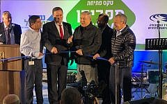 Prime Minister Benjamin Netanyahu (3rd from right) cuts the ribbon at an inaugural ceremony of a new interchange at the central West Bank settlement of Adam on December 11, 2018. (Jacob Magid/Times of Israel)