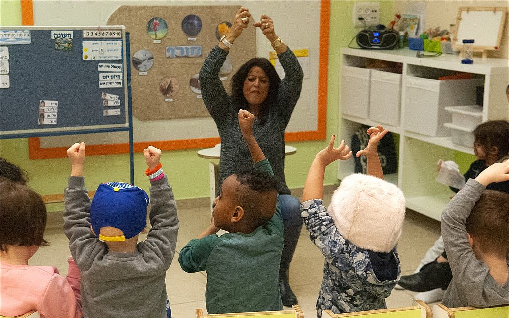 Dorit Zach, a teacher at Larger Than Life's 'Daycare of Dreams' kindergarten in Ramat Gan, leads kids with cancer in a Hebrew-language sing-a-long. (Larry Luxner/ Times of Israel)