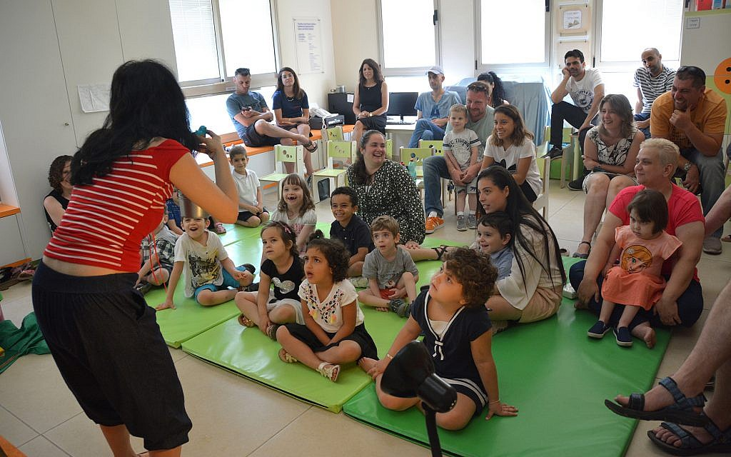 A volunteer gets kids at the Daycare of Dreams kindergarten in Ramat Gan to sing Hanukkah songs. (Courtesy Larger Than Life)