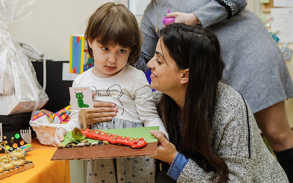 Liron Walter helps a child with cancer put together a menorah for Hanukkah at the Daycare of Dreams kindergarten in Ramat Gan. (Courtesy Larger Than Life)