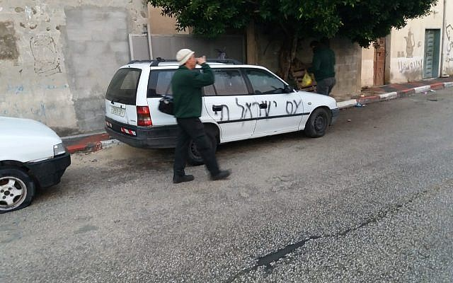 Graffiti daubed on a car in the northern West Bank village of Yasuf reads 'The people of Israel lives,' December 18, 2018. (Muhammad Itiani)