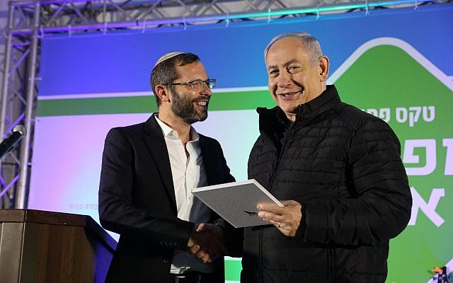 Binyamin Regional Council chairman Yisrael Gantz (L) gives an award to Prime Minister Benjamin Netanyahu at an inaugural ceremony of a new interchange at the central West Bank settlement of Adam on December 11, 2018. (Yossi Zamir)