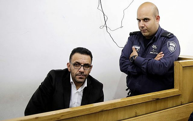 An Israeli policeman watches over the Palestinian Authority's Jerusalem governor, Adnan Ghaith, during a court appearance following his arrest in Jerusalem, November 29, 2018. (AP Photo/Mahmoud Illean)