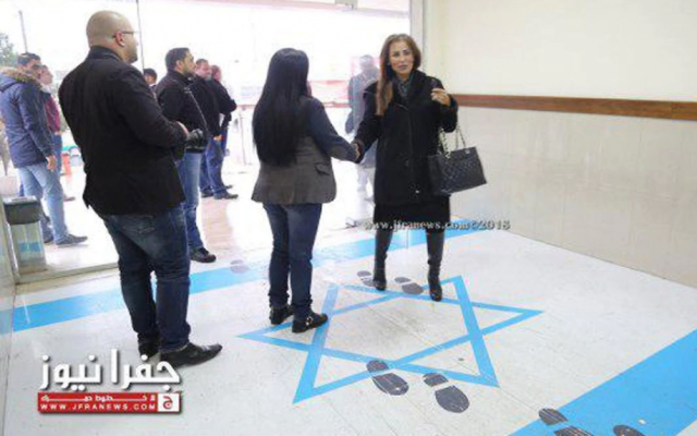Jordan's minister for media affairs and communications and government spokesperson, Jumana Ghunaimat (R), stepping on the Israeli flag at the entrance to the trade union headquarters in Amman, December 2018. (Screen capture: Jamuna TV)