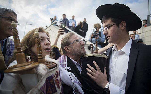 Orthodox Jews try to prevent a group of American Conservative and Reform rabbis, and the Women of the Wall movement members, from bringing Torah scrolls into the Western Wall compound, during a protest march against the government's failure to deliver a new prayer space, at the Western Wall in Jerusalem's Old City, November 2, 2016. (Hadas Parush/Flash90)