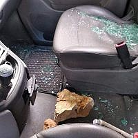 A rock reportedly thrown by Israeli settlers is seen inside of a Palestinian car near the northern West Bank settlement of Yitzhar on December 13, 2018. (B'Tselem)
