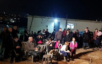 Settlers from Kiryat Arba attend a ceremony at the Mevaser outpost marking the first families to move into the hilltop community in response to recent spate of Palestinian attacks on December 16, 2018. (Kiryat Arba Hebron Local Council)