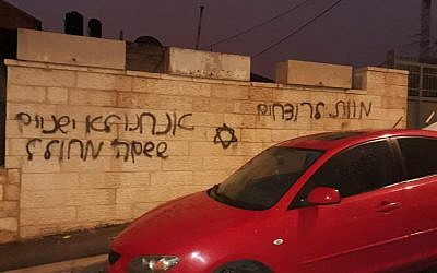 "A car in the East Jerusalem of Beit Hanina whose tires were slashed next to a wall that was gratified with a Jewish star the Hebrew phrases ""Death to murderers"" and ""We don't sleep when the name of God is desecrated"" on December 20, 2018. (Courtesy)"