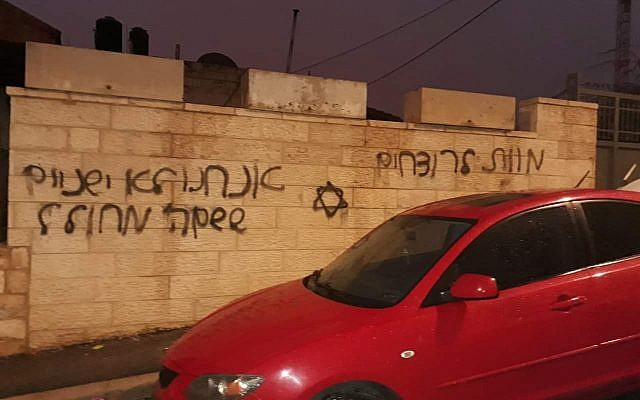 """A car in the East Jerusalem of Beit Hanina whose tires were slashed next to a wall that was gratified with a Jewish star the Hebrew phrases """"Death to murderers"""" and """"We don't sleep when the name of God is desecrated"""" on December 20, 2018. (Courtesy)"""