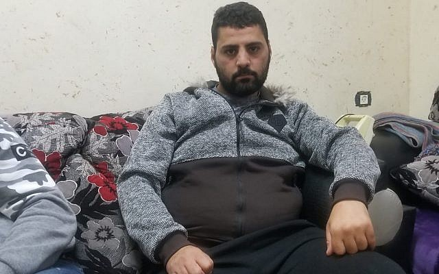 Mohammad al-Abbasi, 25, sitting in the living room of a family member's home in Silwan on December 23, 2018. (Adam Rasgon/Times of Israel)