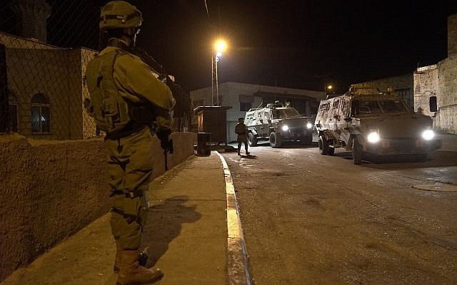 Israeli soldiers search for gunmen who opened fire at a bus stop outside the West Bank settlement of Ofra, injuring seven people, on December 9, 2018. (Israel Defense Forces)