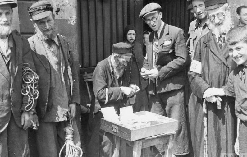 Illustrative: An armband seller in the Nazi-created Warsaw Ghetto, which was in existence from 1940 until the summer of 1943. (public domain)