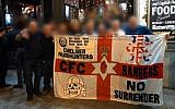 "Chelsea English Premier League soccer fans from the ""headhunters,"" an extremist fan group known for hooliganism, in Budapest on December 13, 2018, holding a banner with a depiction of the SS-Totenkopf, a skull and bones graphic used by the Nazis. (Twitter screen capture)"