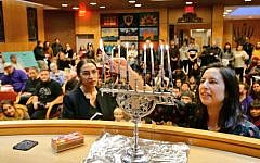 Alexandria Ocasio-Cortez (L) helps light a candle at a Hannukah celebration on December 9, 2018 ( Jews for Racial & Economic Justice/Twitter)