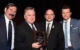 """Rep. Chris Smith holds an award he received at the 36th annual Bet El gala dinner in New York, Dec. 2, 2018. Joining Smith, from left, are Dr. Joseph Frager, Duvi Honig and Pete Hegseth, co-host of """"Fox and Friends."""" (Courtesy of American Friends of the Bet El Yeshiva Center)"""