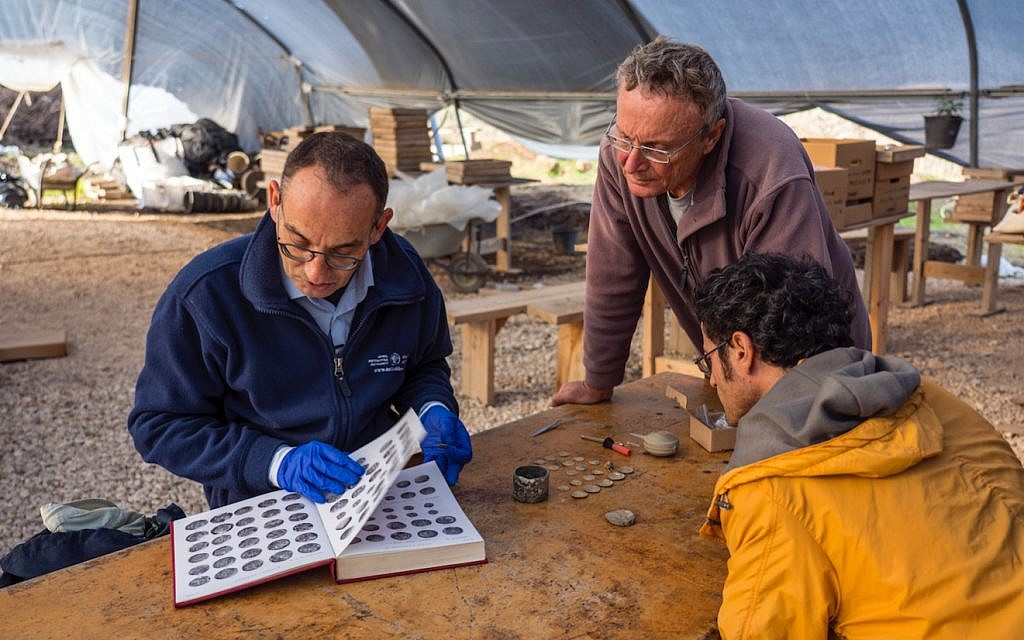 Preliminary identification of the coins discovered at the Caesarea Maritima archaeological site by (left) Dr. Robert Kool, coin expert at the Israel Antiquities Authority, and (standing) dig co-director Dr. Peter Gendelman. (Yaniv Berman, courtesy of the Caesarea Development Corporation)
