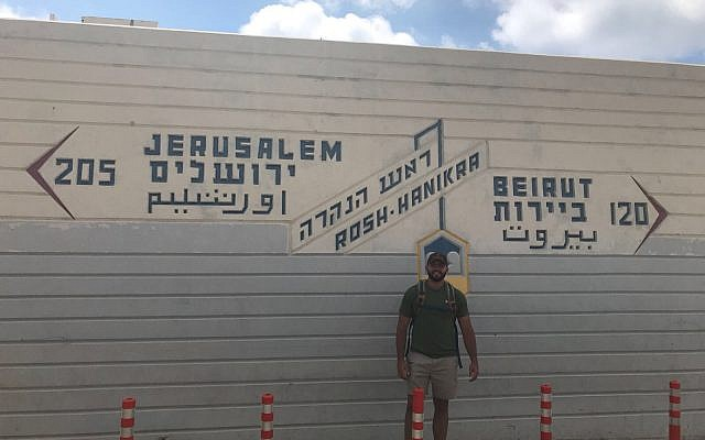 Zachary Zeff stands in front of a sign pointing to Jerusalem, Rosh Hanikra, and Beirut. (Courtesy)