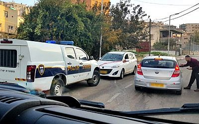 Illustrative: The scene of a drive-by shooting in the Arab Israeli town of Umm al-Fahm that left a 14-year-old boy wounded on December 26, 2018. The white car in the center was the target of the shooting, police said. (Hadashot TV screen capture)