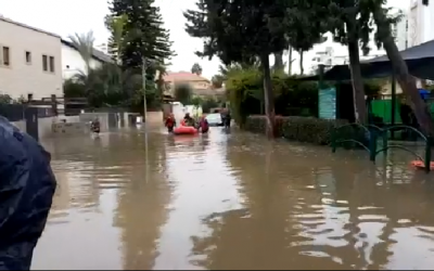 Children being rescued by rubber boats from a flooded preschool in Rehovot amid powerful rains, December 6, 2018. (Channel 10 screen capture)