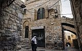 A Palestinian woman walks past a house in the Muslim Quarter of the Old City of Jerusalem which was bought by Jewish Israelis, on December 4, 2019. (THOMAS COEX/AFP)