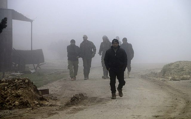 Turkey-backed Syrian fighters walk down a street in the town of Qirata, near the rebel-held border town of Jarabulus, on December 23, 2018. (Bakr ALKASEM / AFP)
