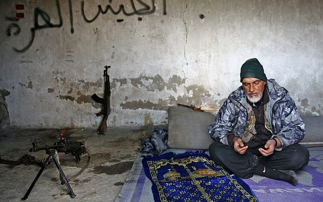 A Turkey-backed Syrian fighter recites a prayer in the town of Qirata, near the rebel-held border town of Jarabulus, on December 24, 2018. (Nazeer AL-KHATIB / AFP)