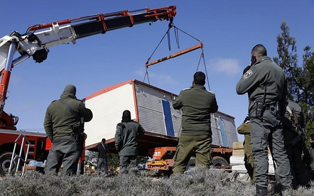 Members of the Israeli security forces remove a caravan that settlers had brought to the former outpost of Amona on January 3, 2019. (Menahem Kahana/AFP)