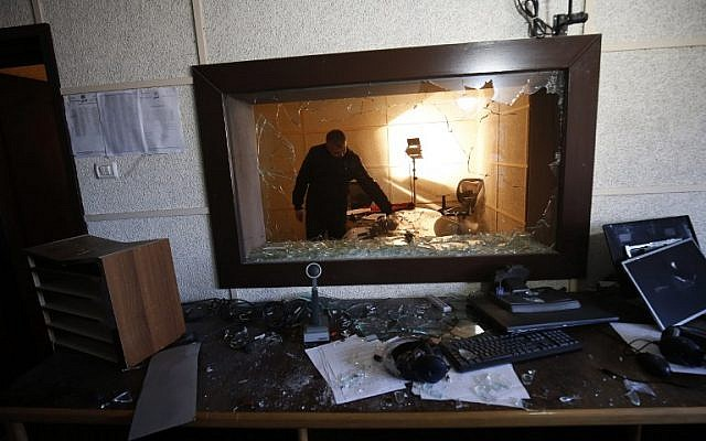 An employee of the Palestinian Authority-run radio and television stations inspects the damage at one of the studios on January 4, 2019, after armed men reportedly raided the building in Gaza City. (Said Khatib/AFP)