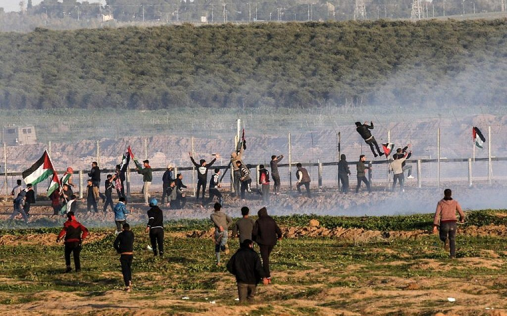 Palestinian protesters try to climb the border fence with Israel during clashes following a demonstration along the border east of Gaza City on January 4, 2019. (Said Khatib/AFP)