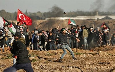 Illustrative: A Palestinian protester uses a slingshot to hurl stones at Israeli forces across the border fence, during clashes following a demonstration along the border with Israel east of Gaza City on January 11, 2019. (Mahmud Hams/AFP)