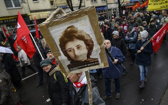 A leftist demonstrator holds a placard featuring a portrait of communist revolutionary Rosa Luxemburg during a march to the Monument for the Socialists at Berlin's Friedrichsfelde Central Cemetery where Luxemburg is buried, on January 13, 2019. (John MACDOUGALL/AFP)