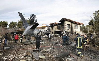Firefighters and security forces gather amidst the debris of a Boeing 707 cargo plane that reportedly crashed into a residential complex near the Iranian capital Tehran with 10 people onboard on January 14, 2019. (HASAN SHIRVANI/various sources/AFP)