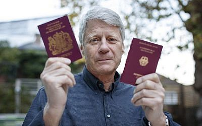 TV presenter Nick Ross poses with his British (L) and German passports at his home in London on November 5, 2018. (TOLGA AKMEN / AFP)