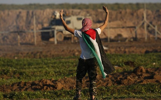 A protester draped in the Palestinian flag gestures at Israeli forces across the border fence, during clashes following a demonstration along the border with Israel east of Gaza City on January 18, 2019. (Said KHATIB / AFP)