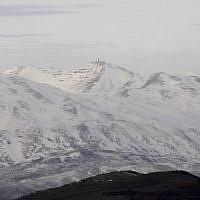 A picture taken from the Israeli side of the Golan Heights shows snow covered mountain inside Syria on January 20, 2019. (JALAA MAREY / AFP)