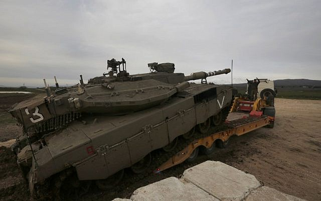 An Israeli army Merkava tank is loaded into a truck in the Golan Heights, on January 20, 2019. ( JALAA MAREY / AFP)