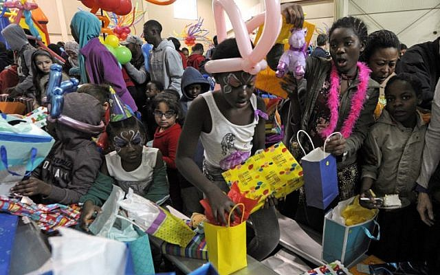 Children open presents during the 2019 Refugee Birthday Party at the Della Lamb Community Center,  n Kansas City, Missouri, January 20, 2019. (DAVE KAUP/AFP)