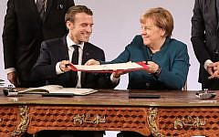 French President Emmanuel Macron and German Chancellor Angela Merkel exchange the French-German friendship treaty during the signing ceremony, on January 22, 2019 in the town hall of Aachen, western Germany. - France and Germany signed a new friendship treaty seeking to boost an alliance at the heart of the European Union as Britain bows out and nationalism advances around the continent. (Photo by Ludovic MARIN / AFP) / ALTERNATIVE CROP