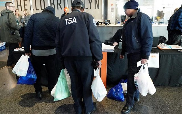 Furloughed Transportation Security Administration (TSA) employees and others leave the Barclays Center with bags of food as the Food Bank For NYC holds food distribution for federal workers impacted by the government shutdown in Brooklyn, New York January 22, 2019. ( TIMOTHY A. CLARY / AFP)
