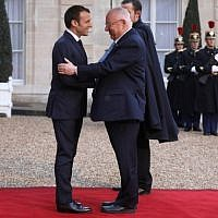 President Reuven Rivlin, right, is welcomed by French president Emmanuel Macron upon his arrival at the Elysee Palace in Paris on January 23, 2019. (Ludovic MARIN/AFP)