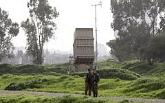 Illustrative. Israeli soldiers stand near a battery of the Iron Dome missile defense system deployed in Tel Aviv on January 24, 2019. (Menahem Kahana/AFP)