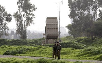 Illustrative: Israeli soldiers stand near a battery of the Iron Dome missile defense system deployed in Tel Aviv on January 24, 2019. (Menahem Kahana/AFP)