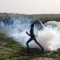 A Palestinian protester throws back a tear gas canister towards Israeli forces during clashes following a demonstration along the border with Israel, east of Gaza City on January 25, 2019. (MAHMUD HAMS / AFP)
