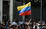 """A crowd of opposition supporters listen to Venezuela's National Assembly head and the country's self-proclaimed """"acting president"""" Juan Guaido (out of frame), at Bolivar Square in Chacao, eastern Caracas, on January 25, 2019. (Photo by Federico PARRA / AFP)"""