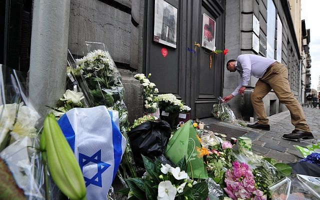 File: A man lays flowers as he pays his respects in front of a makeshift memorial at the entrance of the Jewish Museum in Brussels, where a deadly shooting took place the day before, killing four, May 25, 2014 (Georges GOBET / AFP)