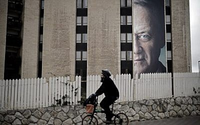 A man rides a bycicle past a political campaign poster of former IDF chief of staff Benny Gantz, in Jerusalem, on January 28, 2019. (THOMAS COEX / AFP)