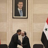 Syrian Prime Minister Imad Khamis, right, and Iranian Vice President Eshaq Jahangiri shake hands after the signing of an agreement in the capital Damascus on January 28, 2019. (LOUAI BESHARA / AFP)