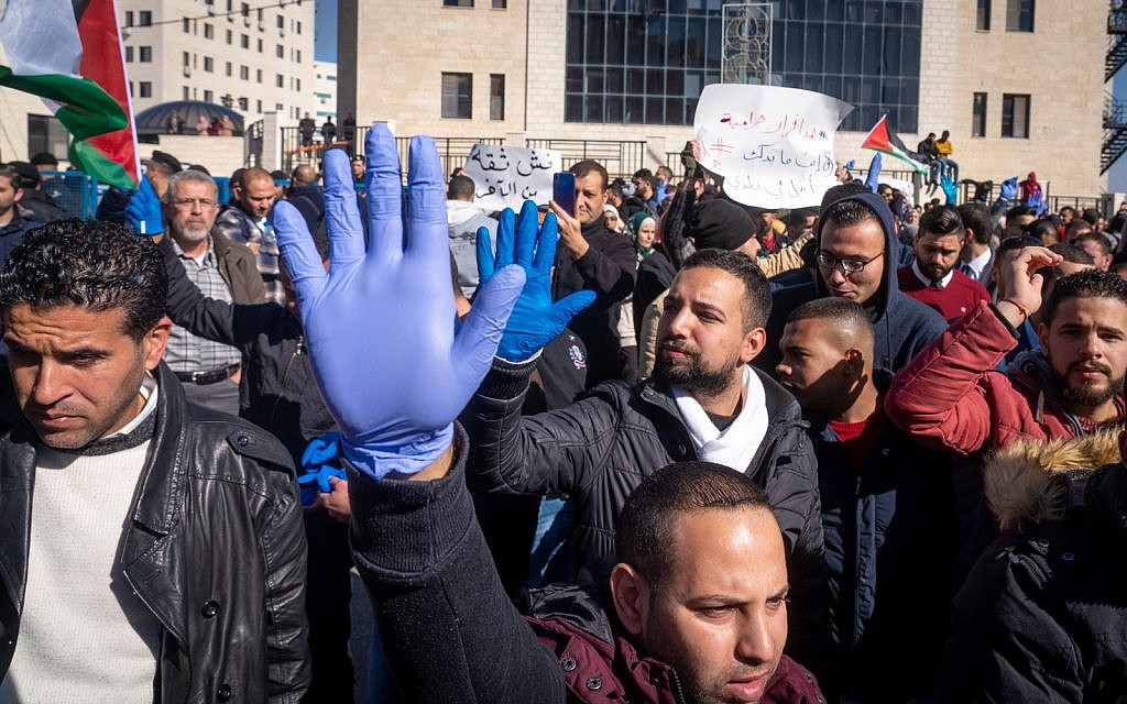 Palestinians protest against a government tax hike in Ramallah, West Bank, December 12, 2018. The blue gloves are a unifying symbol for the protesters, compared to the yellow vests worn by protesters in recent demonstrations in France. (Luke Tress/Times of Israel)