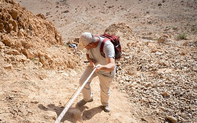 Researcher Oren Gutfeld descends from Cave 52, at the Qumran archaeological site, January 22, 2019. (Luke Tress/Times of Israel)