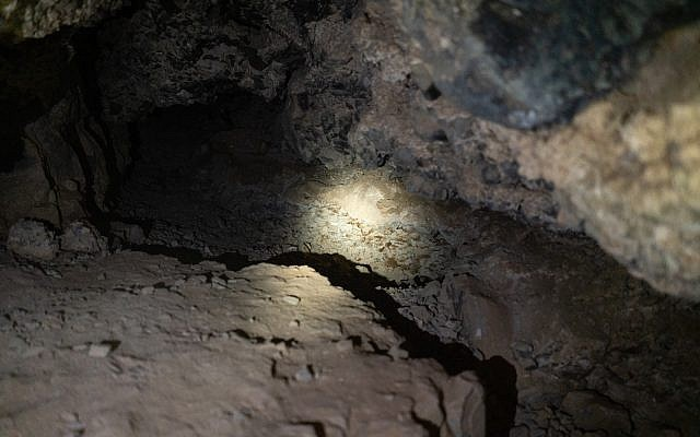 A researcher shines a flashlight on the spot inside a cave where Dead Sea Scroll jars were discovered in a recent excavation at Qumran, January 22, 2019. (Luke Tress/Times of Israel)